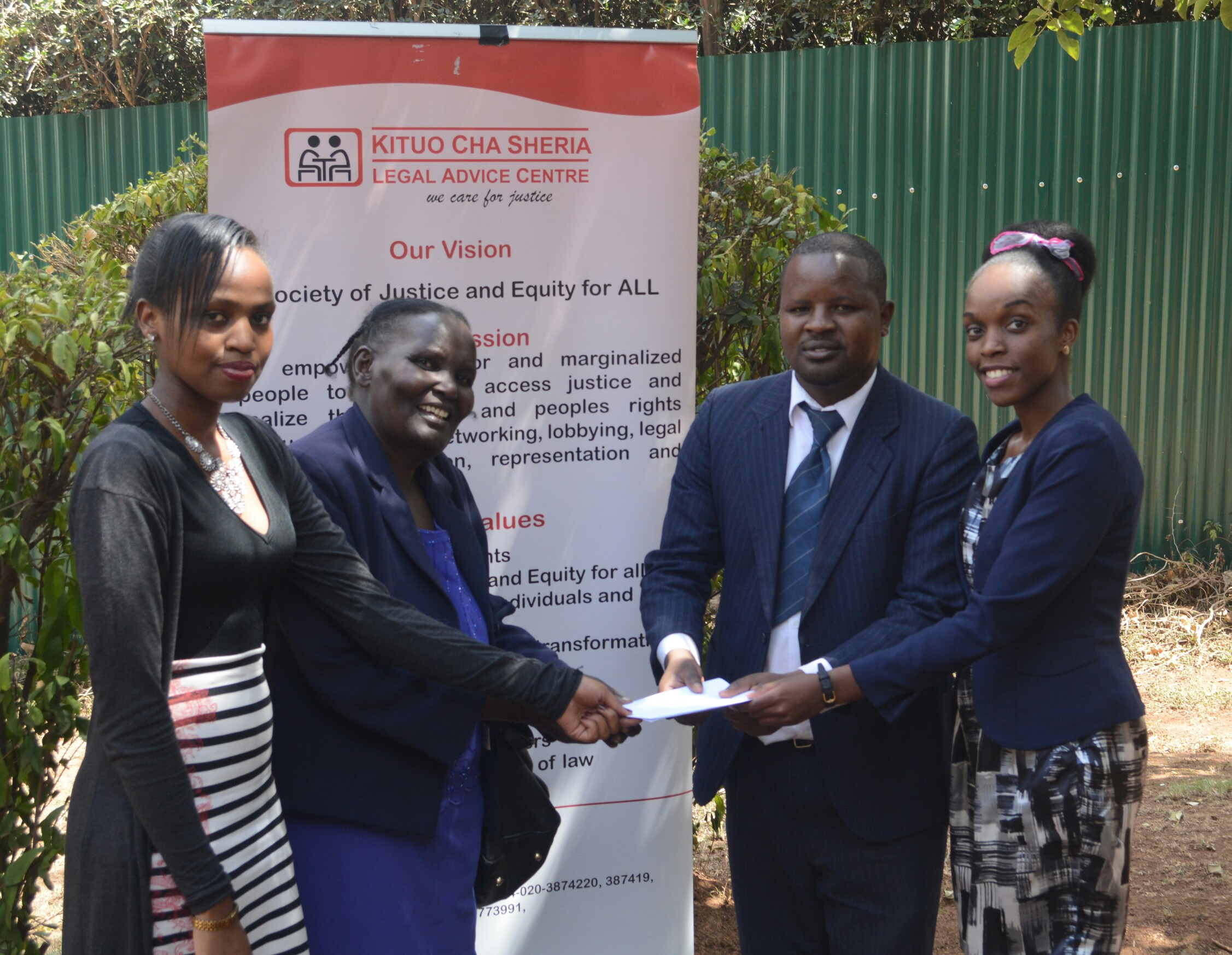 John Mwariri handing over the court judgement to Mary Nduku