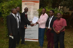 Samuel Nzuki Mutisya receiving a copy of judgment from Kituo advocates